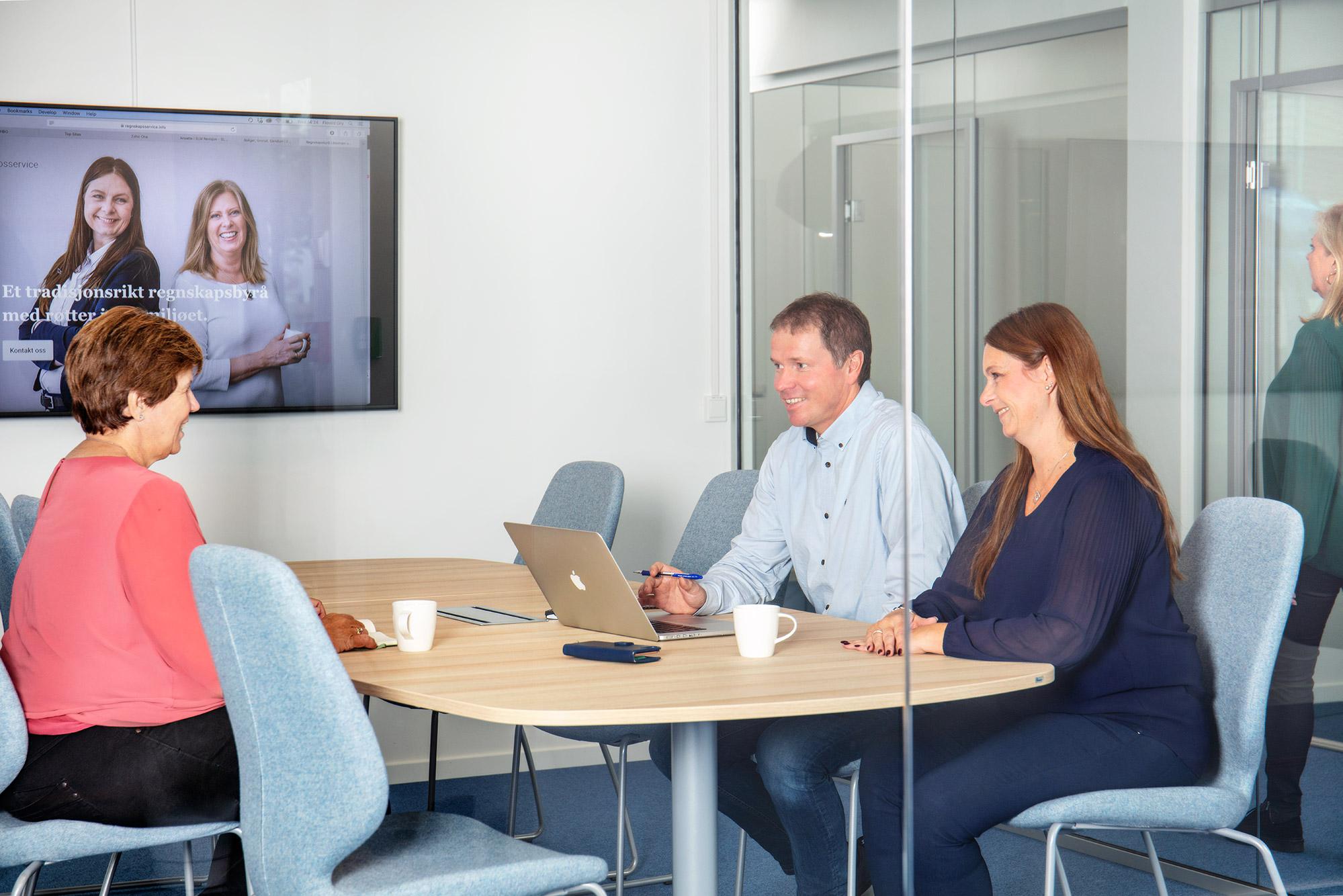 Bildet viser menneskene som jobber i REGNSKAPSSERVICE. Menneskene sitter inne på et møterom.